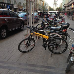 View enlargement of Bicycles and motorcycles are lined up on the footpath.