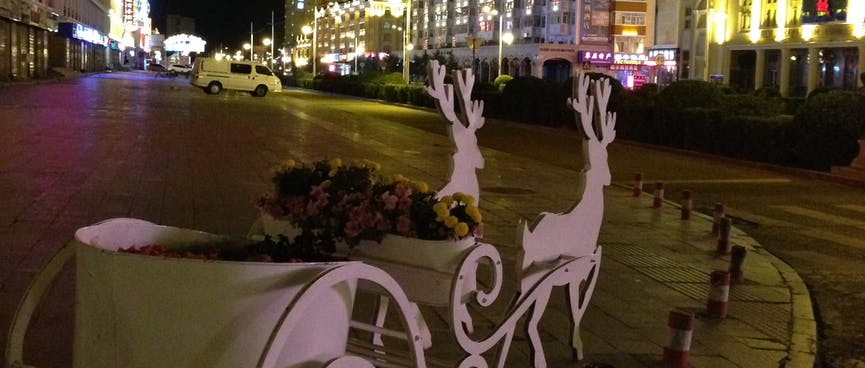 A cut out sleigh hosts an overflowing flower pot.