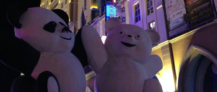 A panda and a polar slap paws on a street corner.