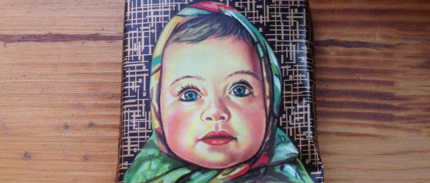 A chocolate wrapper has an illustration of a baby in a head scarf,