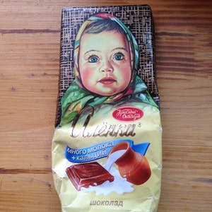 View enlargement of A chocolate wrapper has an illustration of a baby in a head scarf,