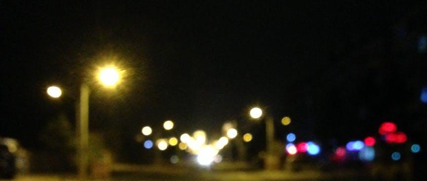 Blurred spheres light an urban street.