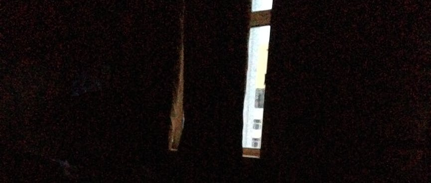 A thin strip of daylight is visible through the parted curtains.