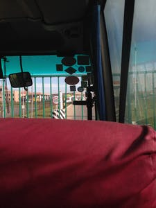 A green gate and a bilingual Stop sign stop us from covering the last short stretch of road into Russia.