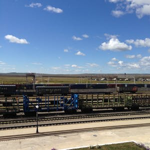 View enlargement of Empty railway wagons wait patiently in the hot midday sun at Zabaikalsk.