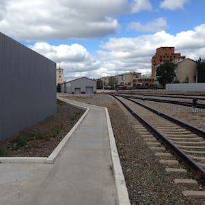 View enlargement of A clean and angular concrete path runs parallel to railway tracks, at Zabaikalsk station.