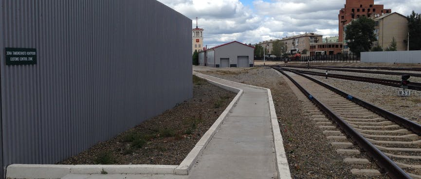 A clean and angular concrete path runs parallel to railway tracks, at Zabaikalsk station.