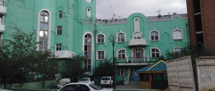 A three story apartment block with interesting arched windows, in Zabaikalsk.