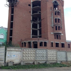 View enlargement of A curved six story brick is held together by scaffolding, at Zabaikalsk.