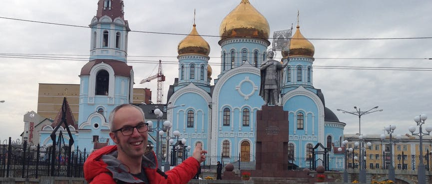 A pale blue four story church with golden onion domes and a tall tower, opposite Chita's Railway Station.