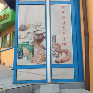 View enlargement of A poster advertises bread, cheese, sausage, milk and fruit juice, in Chita.