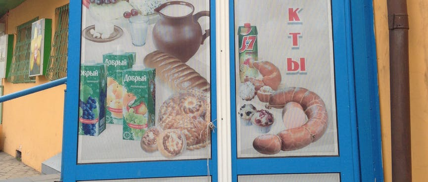 A poster advertises bread, cheese, sausage, milk and fruit juice, in Chita.