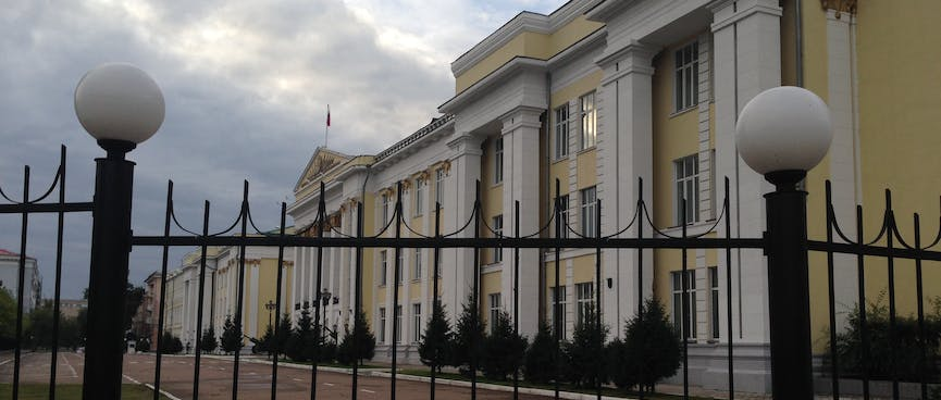 Four story yellow buildings with white rectangular columns sit behind tall metal gates, in Chita.