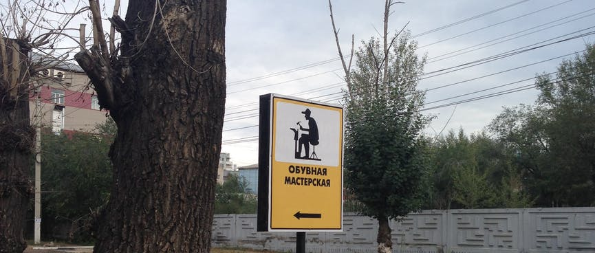 A roadside sign depicts a man hammering a new sole onto an upturned boot, in Chita.