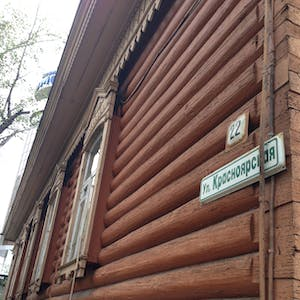 View enlargement of Wooden half-rounds cover the wall of an ancient log cabin, in Chita.
