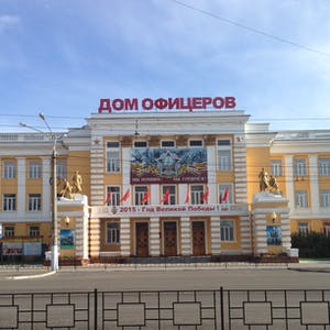 View enlargement of Bronze statues of soldiers stand guard outside a solid yellow building, in Chita.