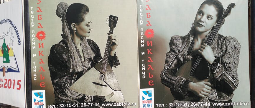 Pretty women cradle triangular and ovalular guitars in their arms.
