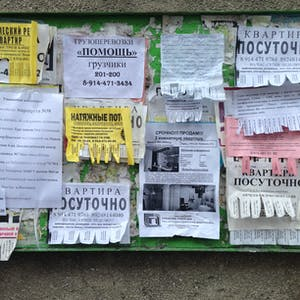 View enlargement of Real estate, printed and handwritten advertisements on a noticeboard, in Chita.