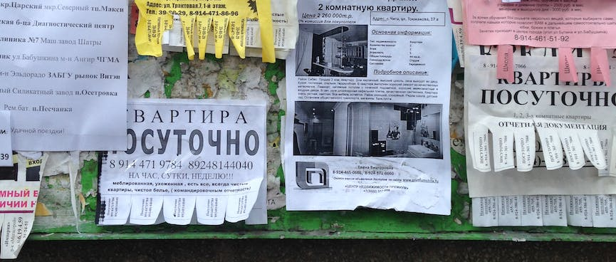 Real estate, printed and handwritten advertisements on a noticeboard, in Chita.