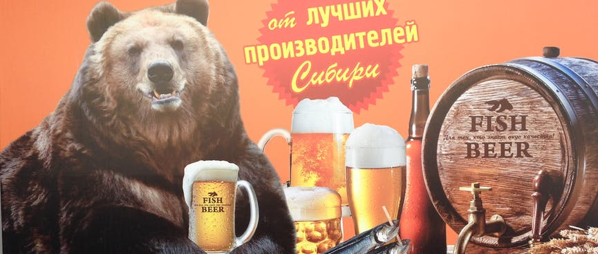 A large brown bear holds a large glass of beer between his paws.