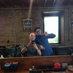 View enlargement of Germin leans on my chair while I take a photo of us in the mirror, at Bros hair salon in Chita.