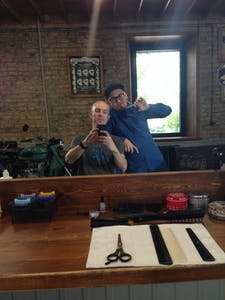 Germin leans on my chair while I take a photo of us in the mirror, at Bros hair salon in Chita.