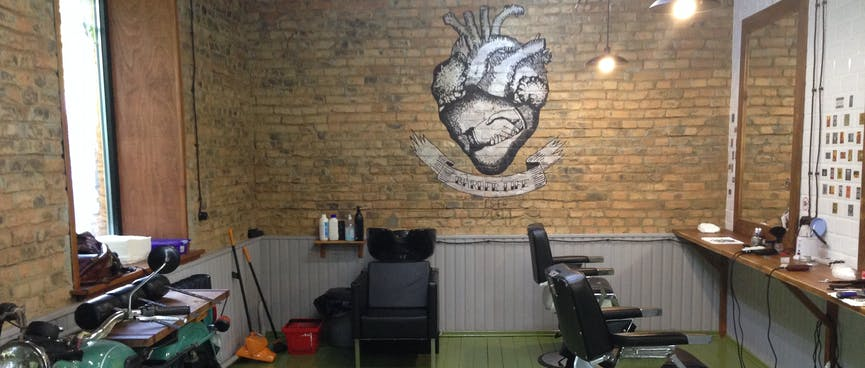 A row of barber chairs, an old motorcycle, and a illustration of a heart and two hands shaking.
