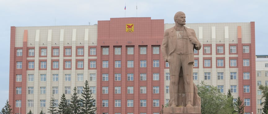 A large statue of Lenin, on a pedestal outside an eight story building with many windows, in Chita.