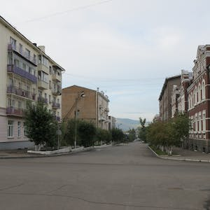 View enlargement of Three story apartment blocks line a deserted street, in Chita.