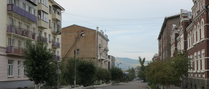 Three story apartment blocks line a deserted street, in Chita.