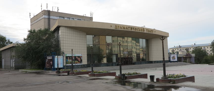 A squat building with a curved frontage, reflective windows and tiled walls, displays a few stage play posters, in Chita.
