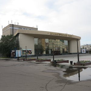 View enlargement of A squat building with a curved frontage, reflective windows and tiled walls, displays a few stage play posters, in Chita.