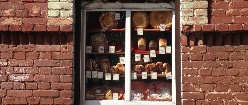 An arched window cut out in a brick wall hosts an elaborate display of baked goods, in Chita.