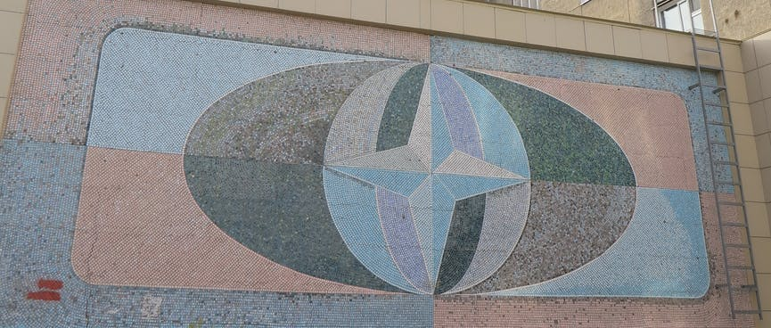 A mural is split into quadrants, and features a four point star on top of an oval globe, in Chita.