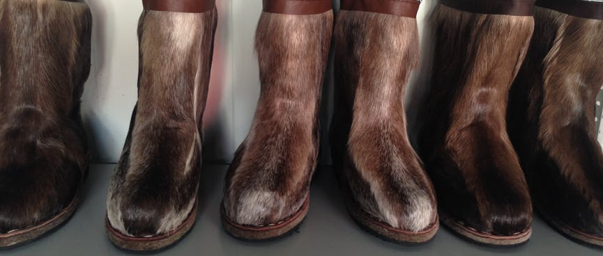 A shelf of brown fur boots look like horse legs.
