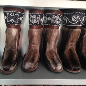 View enlargement of A shelf of brown fur boots look like horse legs.