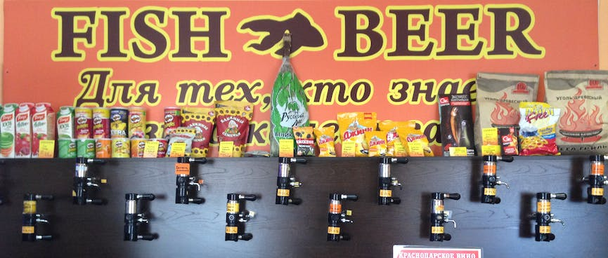 Beer taps cover a wall under a large sign stating FISH BEER, in Chita.