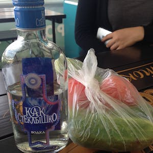 View enlargement of Half a bottle of vodka and a bag of tomatoes and cucumbers.