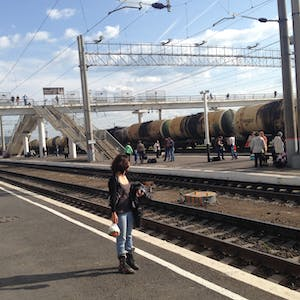 View enlargement of Wanna stands on an empty platform while a long line of tanker wagons roll by, in Chita.