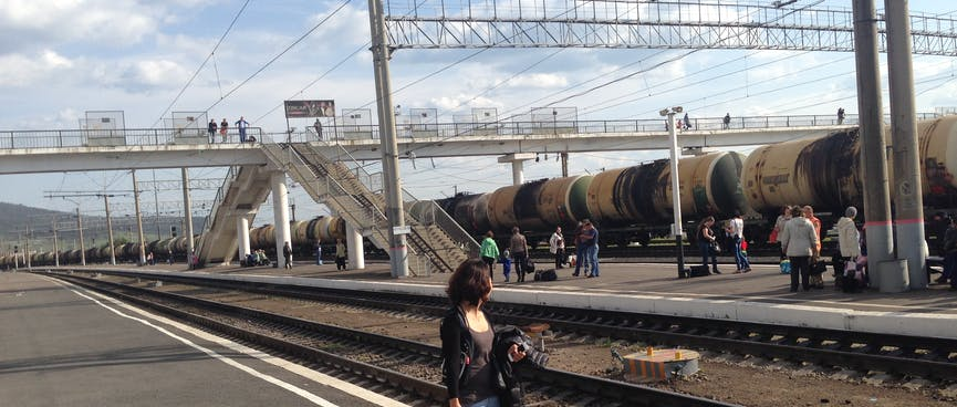 Wanna stands on an empty platform while a long line of tanker wagons roll by, in Chita.