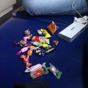 View enlargement of Wanna sits next to a large pile of candy.
