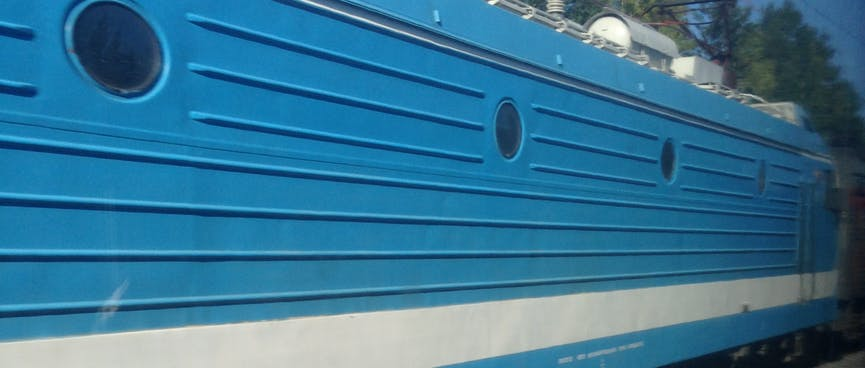 A mid blue locomotive with small portholes and horizontal metal ribbing.