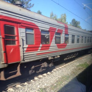 View enlargement of A large red Russian Railways logo brightens up a grey passenger carriage.