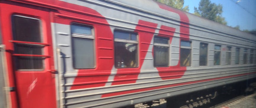 A large red Russian Railways logo brightens up a grey passenger carriage.