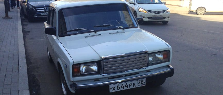 A shiny white Lada is parked on a side street.