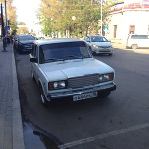 View enlargement of A shiny white Lada is parked on a side street.