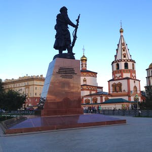 View enlargement of A statue of a Cossack soldier holding a rifle, and some ornate buildings.