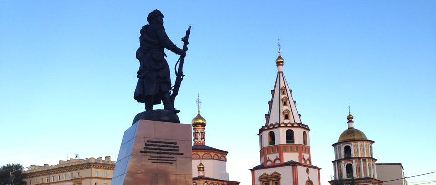 A statue of a Cossack soldier holding a rifle, and some ornate buildings.