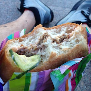 View enlargement of Thick bread buns, a layer of meat, and a floppy piece of cucumber.