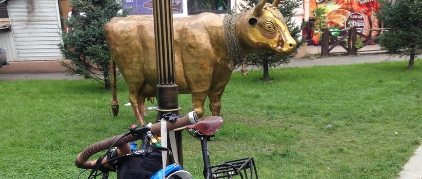 My bike leans against a lamppost, in front of a bronze bull, in Irkutsk.